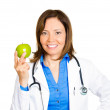 Doctor pointing at green apple — Stock fotografie