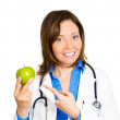 Doctor pointing at green apple — Stock Photo
