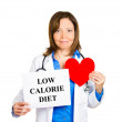 Cardiologist with stethoscope holding sign low calorie diet — Stock Photo #43716143