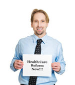 Man holding health care reform now! sign — Stock Photo