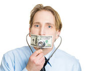 Professional placing stethoscope to hundred dollar bill taped to mouth — Stock Photo