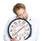 Exhausted doctor sleeping on large clock — Stockfoto