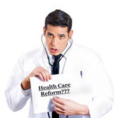 Doctor listening to the sign that says healthcare reform now — Stock Photo