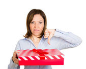 Woman holding gift in one hand, thumbs down with other — ストック写真