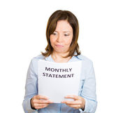 Woman looking disgusted at her monthly statement — Stockfoto