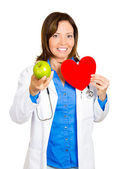 Doctor holding a heart to chest and offering apple — Stock Photo