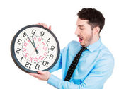 Guy holding clock looking anxiously — Stock Photo