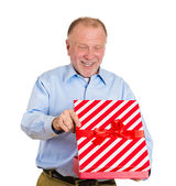 Excited senior mature man about to open unwrap red gift box — Stock Photo