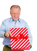 Mature man holding gift box, very displeased — Stock Photo