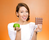 Woman offering apple as an alternative to chocolate — Stock Photo