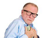 Mature man holding dollar banknotes tightly — Stock Photo