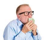Mature man kissing dollar banknotes in hand — Stock Photo