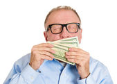 Mature man smelling dollar banknotes — Stock Photo