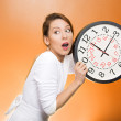 Woman holding clock looking anxiously — Stock Photo #44000079