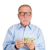 Mature man counting dollar banknotes — Stock Photo