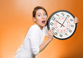 Woman holding clock looking anxiously — Stock Photo