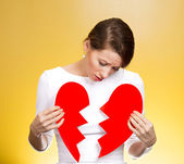 Confused woman holding broken heart — Stock Photo