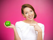Woman pointing at yellow apple — Stock Photo