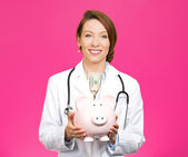 Doctor holding piggy bank — Stock Photo