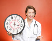 Doctor holding clock and pills — Stock Photo
