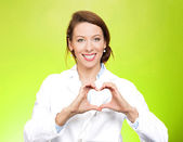 Smiling doctor making heart sign with hands — Stock Photo