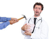 Doctor protecting piggy bank — Stock Photo