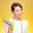 Woman with apple, measuring tape wrapped around — Stock Photo #44021549
