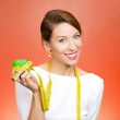Woman holding apple, measuring tape wrapped around — Stock Photo #44021687