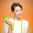 Woman holding apple, measuring tape wrapped around — Stok fotoğraf