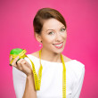 Woman holding apple, measuring tape wrapped around — Photo