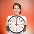 Happy woman holding wall clock — Стоковое фото