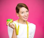 Woman holding apple, measuring tape wrapped around — Stock Photo