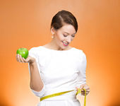Woman holding green apple, measuring her waist — Stock Photo