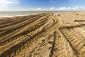 Caterpillar Tracks from digger on stony beach — Stock Photo