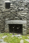 Old fireplace in ruined slate house — Stock Photo