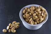 Dry roasted peanuts in white ramekin on slate — Stock Photo