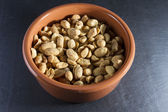 Dry roasted peanuts in terracotta  ramekin on slate. — Stock Photo