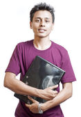 Young Man Smiling Carrying a Laptop — Stock Photo