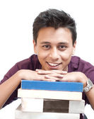 Young Man Smiling with Chin on Books — Stock Photo