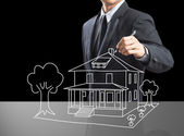 Business man drawing dream house on screen — Stock Photo