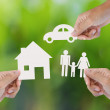 Hand holding a paper home, car, family on green background — Stock Photo #42395795