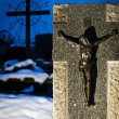 Grave stone with a Jesus figure and a cross on All Saints Day — Stock Photo