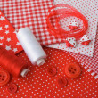 图库照片: Accessories for sewing: threads, fabric, buttons in red-white co
