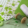 图库照片: Accessories for sewing: threads, fabric, buttons in green-white