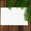 Empty paper form with fir-tree branches on old wooden background — Stock Photo #33900511
