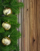 Christmas fir-tree with golden baubles on a wooden background — Stock Photo