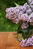 Bouquet Lila dans un broc en verre sur une table en bois contre les verts — Photo