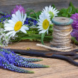 Wild flowers, scissors and hank of threads on an old wooden back — Stock Photo #49152085
