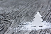 White wooden fir-tree in snow on an old wooden background — Stock Photo