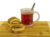 A glass cup with tea and biscuit roulade — Stock Photo